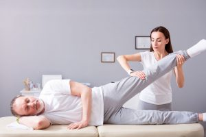 Man PT - personal treatment. glad male patient lying down with female concentrated and serious physiotherapist performing some stretch exercises on mans leg